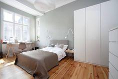Stonowany wystrój tej sypialni bazuje na charakterystycznych dla stylu skandynawskiego elementach – drewnie, pastelowych chłodnych kolorach, białych meblach. Proste łóżko z tapicerowanym zagłówkiem oświetlają oryginalnie designerskie lampy Tolomeo marki Artemide. Przy wielkim oknie z kolei zorganizowano miejsce do pracy ze zgrabnym biurkiem na drewnianych koziołkach.