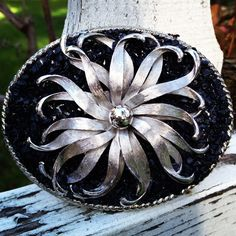 Unique vintage silver brooch on a beautiful black onyx stone chip background