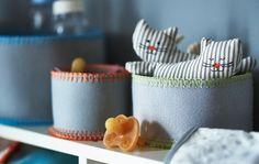 Plstěné košíky s dětskými hračkami a dudlíky