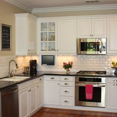 white subway tile backsplash. dark countertops.  white cabinets. brushed silver drawer pulls.