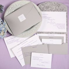 A white invitation card is wrapped in a grey pocket mailer featuring a floral design on the inside. Enclosure cards are available to complete this ensemble.