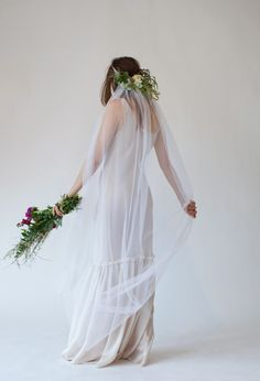 Veil trail.  Love the flowers at the back of the head.  This adds interest when taking vows with back turned to guests.