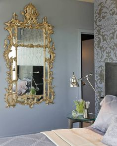 Blue and gray bedroom features accent wall clad in gray and blue damask wallpaper lined with a gray velvet wingback bed accented with silver nailhead trim dressed in blue silk bedding beside a glass-top bedside table under a polished nickel swing-arm sconce situated across form a gray wall lined with ornate gilt mirror.