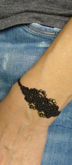 Ein geknüpftes **Armband** in Schwarz mit Glasschliffperlen.  Es ist…