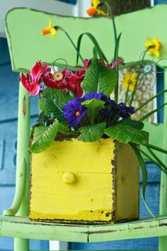 Beautiful yellow wooden drawer filled with colourful flowers on a bright green chair. So pretty!