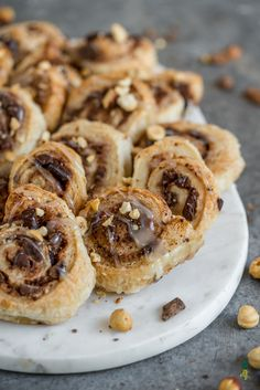 Easy to make, 5-ingredient puffed pastry cinnamons rolls are the perfect decadent dessert. Topped with hazelnuts and a cream cheese glaze and oozing with chocolate, cinnamon, and sugar, you won't be able to have just of these flaky puffed pastry rolls!