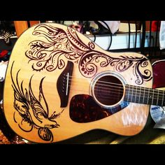 This is my guitar! I spent forever designing and sketching this work of art on my beautiful Yamaha dreadnaught acoustic guitar. The bird and the tree in the wind design is the best one I have done to this day. I have done one other and I am working on silver over a black finish guitar for a friend. Sharpie comes off with expo... Makes the whole process easier in the end because I have a personal eraser! :) anyway- I think this is beautiful and cool! :) line drawings almost always are