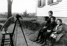 "Photograph shows three members of the Payro family being ""photographed"" by their cat in November, 1909"