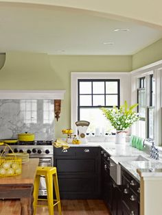 A Pop of Yellow  Italian marble tops the kitchen's custom cabinetry, while salvaged Victorian corbels serve as distinctive brackets for the stove's hood. An industrial steel stool gives the otherwise neutral room a jolt of bright color    Read more: Kitchen Designs - Pictures of Kitchen Designs and Decorating Ideas - Country Living