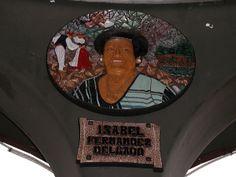 ISABEL FERNÁNDEZ DELGADO (Moratalla, 1927 - Santurtzi, 2017). Mural discoidal realizado en mosaico de tesela cerámica y modelado por Paco Presa Merodio (Torrelavega, 1961 -). Ubicado en 2013 en el interior del kiosco de música para homenajear a popular personaje, muy implicada con el grupo de danzas y las actividades culturales del barrio. Junto a su imagen aparece  una escena de dantzaris, las manos de una espatadantza y una vista desde el mar del barrio en la lejanía.