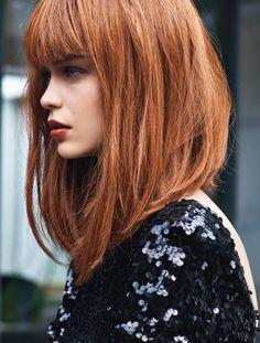 couleur cuivrée, cheveux avec coupe carré dégradé avec frange, robe noire pailletée, frange sur le front