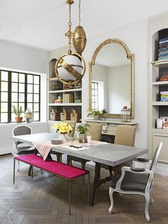 Designer and HGTV host Genevieve Gorder chose mismatched furniture for a more easygoing look in her dining room. A local blacksmith made the zinc-topped table, and around it sit a mixed bag of seats, including armchairs and a fuchsia bench. See more of this home from HGTV Magazine.