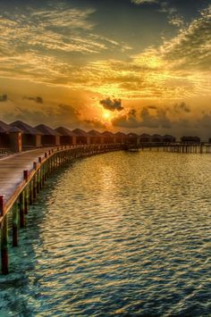 Sunset over bungalows on stilts in Tahiti; French Polynesia.