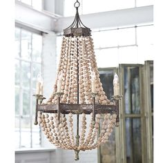 Casual elegance at its finest, the Wood Bead Chandelier is a stunning light fixture. Made of large wood beads that cascade through an antiqued metal scalloped frame with 8 lights, 65 max wattage each.