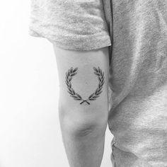 Laurel wreath tattoo on the back of the left arm.