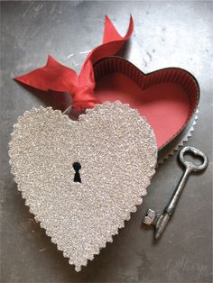 Keyhole Heart Candy Container. Could DIY easily: buy any heart-shaped candy box, cut slightly larger heart out of cardstock with scalloped-edge scissors, attach. Cut keyhole from one side from inside. Cover with glue, then glitter. Voila!