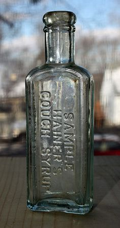Sample Hainer's Cough Syrup - aqua, rectangle, tooled double ring lip, 4 1/8in (106mm) tall. Embossing: SAMPLE / HAINER'S / COUGH SYRUP (down back), C.B. MATHIS (down side), TOMS RIVER, N.J. (down other side) - a few vent hole bumps. - around 1885. Old Medicine Bottles, Antique Glass Bottles, Vintage Bottles, Bottles And Jars, Toms River, Cough Syrup, Double Ring, Message In A Bottle, Black Glass