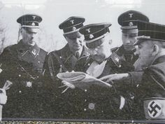 Heinrich Himmler looking over something with Reinhard Heydrich and other SS leaders