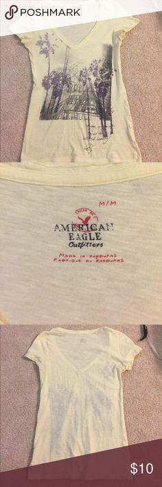 American Eagle V-neck Shirt American Eagle V-neck shirt size MEDIUM. Baby yellow with faded purple palm trees on the front and the Eiffel Tower very faint in the background and cursive handwriting in the bottom right hand corner. Nothing on the back. American Eagle Outfitters Tops Tees - Short Sleeve