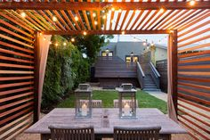 This beautiful shot is from the inside of a wooden patio strung with dainty lights. You can see that the back of the home uses the same unique wood as fencing around the deck. Design: http://www.baranstudio.com/#utm_sguid=163048