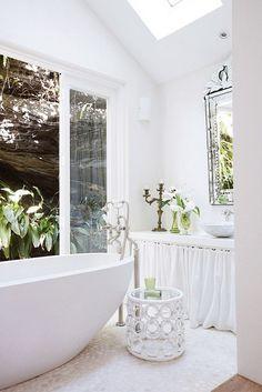 Gorgeous exotic white bathroom with antique mirror, sliding door, and candelabra