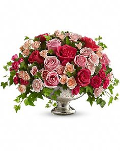 Queen's Court by Teleflora Flower Arrangement - A wide range of hot pink, fuchsia and light pink roses are combined with ivy and variegated pittosporum in a vintage-style Mercury Glass Bowl.