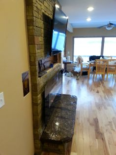 Stamped brick concrete indoor fireplace with custom concrete hearth by Architectural Concrete Solutions.