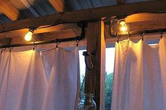 how to make curtain rods from plumbing parts, outdoor living, porches, reupholster, window treatments, DIY curtain rods string lights and drop cloth curtains for a covered porch