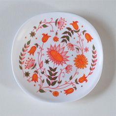 <p>Lot de 4 assiettes vintage en mélamine avec dessin de fleurs orangées, marqué Voluform made in France, quelques rayures d'usage, état d'usage. A coordonner avec le plat assortie pour un joyeux pique-nique!</p>