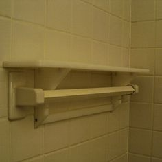 This dead-simple shelf system slips behind any bathroom towel bar to create a narrow shelf for toiletries (without blocking said bar)