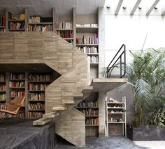 The bookcase in this house spans one wall of the lounge and its uppermost shelves are accessed by a board-marked concrete staircase. It features cantilevering steps and leads up to a narrow gallery overlooking the lounge.