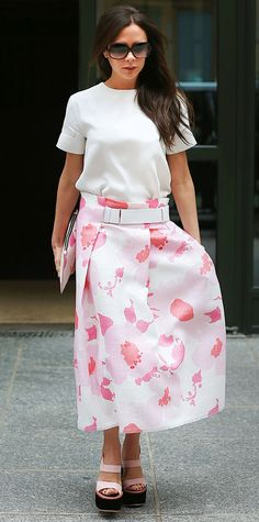 Victoria Beckham took a break from her signature menswear-inspired tailoring and tapped her girly side with a sweet printed pale pink midi-length skert that she styled with a white top, a matching pink clutch, and pink platform sandals.