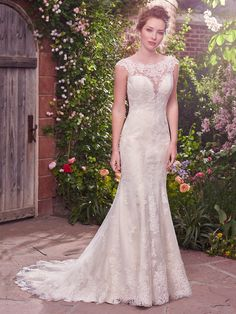 Julie Wedding Dress | Rebecca Ingram. Flirty lace appliqués cascade down this sheath gown, featuring an illusion plunging sweetheart-neckline, open back with illusion lace trim, and scalloped lace hemline. Finished with covered buttons over zipper closure.