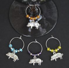 PIG WINE CHARMS-This is a set of 4 pig wine charms. Perfect for the pig collector or farm lover!  Matte seed beads in aqua, yellow, orange, and purple were used, along with shiny silver accents.  Contact me for different colors to create your own custom set.