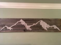 Mountain string art. We took three old fence boards and nailed them together. Hand drew mountains on several pieces of paper to cover the boards then hammered in nails along the border of the drawing. Then used white yarn to string across the nails until most of the space was covered.