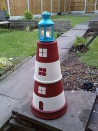 A terracotta lighthouse: 2 large pots, cemented together and painted, with a lantern on top.