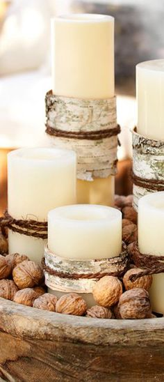 Birchwood Wrapped Candles nestle in a wooden tray with walnuts.