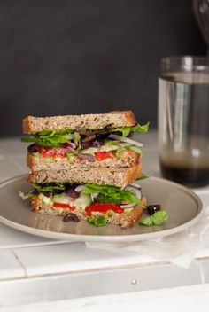 Greek avocado sandwich - My favorite Greek salad ingredients sandwiched between layers of bread smothered with avocado and pesto. A satisfying easy vegetarian meal.
