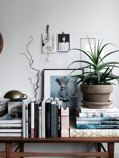 Layered books gives a cool and relaxed styling - love it with the prints on the wall and the big aloe vera plant #interiors