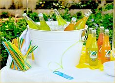 Mexican theme dinner party decor/food: Jarritos stored in metal bucket with colourful straws. Tie the bottle opener to the tub.