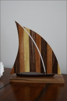 Handcrafted Wood Sailboat - This sailboat is handcrafted with five different hardwoods. The base is Red Maple, the hull is Peruvian Walnut, and the sails are Yellow Heart, Walnut, and African Mahogany hardwoods laminated together.   This makes a great gift for many occasions including Birthdays, 5 Year Anniversary, or for yourself. Sailboat Lovers, Sailboat Collectors, or Nautical Lovers of all ages will love it.