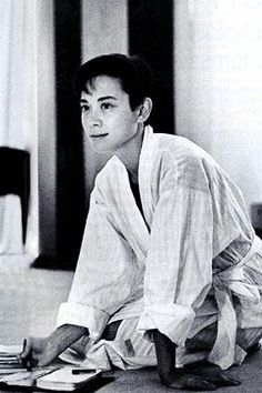 Tina Chow.  She appears to be  happily sketching - maybe  a jewelry design? - or writing.
