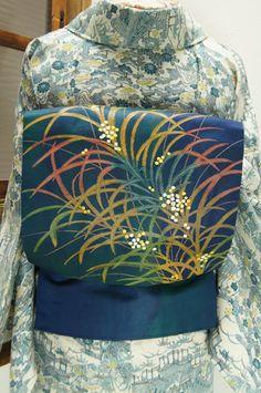 深い紺に、優美な曲線を描く葉と、水玉のような可憐な実をつけた植物模様が織り出された名古屋帯です。