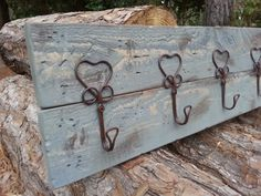 "This rustic coat rack is made from locally milled cypress wood. Built out of two hand picked planks then distressed for character and charm. Finished with a light ""weathered wood"" stain to let the natural texture of the individual boards to be seen. Five farmhouse styled wire heart hooks are attached with antique brass screws.  Measurements: 26"" Long x 7"" Tall"