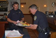 Officer Gantt (L) schools Officer Militano (R) on proper food service at a community outreach event.