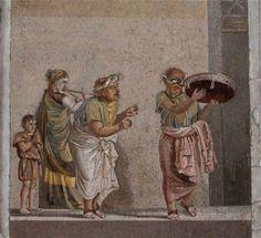 musiciens ambulants - mosaïque - Maison de Cicéron - Pompéi. Famille de musiciens qui participent à une scène des Atellanes, farces populaires représentées à Atella, ville des Osques de l'ancienne Campanie. Cette œuvre, signée du mosaïste grec Dioscoride de Samos, provient de la villa de Cicéron dont on ne voit aujourd'hui plus que la façade. La mosaïque, conservée au musée de Naples, représente 4 personnages dont 3 musiciens affublés de maques typiques de la comédie nouvelle