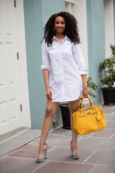A fashionable guest is seen slaying the streets of New Orleans in striped heels and a menswear shirt dress during ESSENCE Festival 2017 | ESSENCE.COM