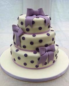 Round three tier white and purple polka dot wedding cake decorated with three large handmade purple fondant bows.From www.novelty-cakes... ........ #wedding #cake #birthday