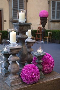 Beautiful pink pomanders decorate a table of pillar candles.