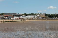 The tide recedes from Hunstanton Promenade, leaving the wet sand exposed, and reflecting the houses and the blue sky